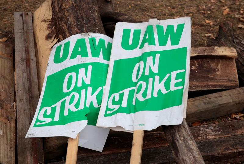 """""""UAW on strike"""" picket signs lay on a pile of wood outside the General Motors Detroit-Hamtramck Assembly in Hamtramck"""