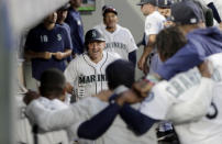 Teammates stand arm-in-arm as they wait to celebrate with Seattle Mariners' Kyle Seager, center, after Seager hit a solo home run against the Detroit Tigers during the fifth inning of a baseball game, Thursday, July 25, 2019, in Seattle. (AP Photo/Ted S. Warren)
