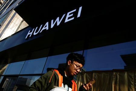 FILE PHOTO: A man uses his phone as he walks past a Huawei shop in Beijing, China, December 19, 2018.  REUTERS/Thomas Peter/File Photo