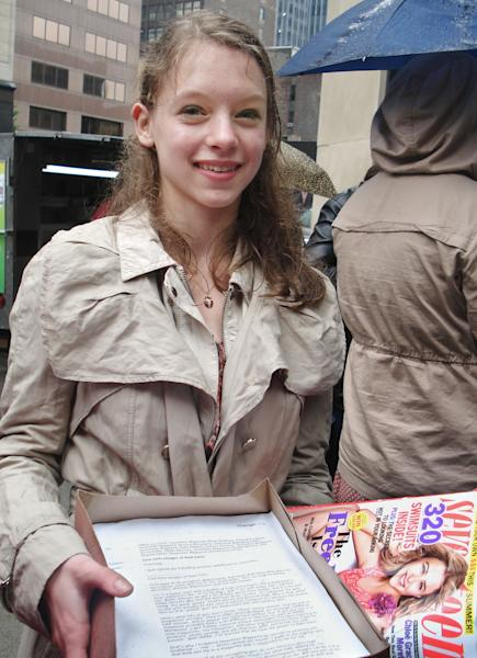 """In this May 2, 2012 photo, Julia Bluhm of Waterville, Maine, holds petitions to """"Seventeen"""" magazine as she leads a protest outside Hearst Corp. headquarters in New York. Bluhm delivered the petition of about 25,000 names and met with officials from the magazine urging them to publish one spread a month of model photos that have not been altered. She says images of young girls in the magazine present an impossible ideal for today's teens. Seventeen's Editor-in-Chief Ann Shoket responded to the campaign in the August issue with a letter acknowledging readers' concerns and vowing never to alter girls' bodies or faces, giving Bluhm more than she'd asked for. (AP Photo/Leanne Italie)"""