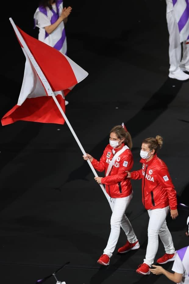 Team Canada's flag-bearer Priscilla Gagné, left, leads her delegation during the opening ceremony of the Tokyo 2020 Paralympic Games, assisted by training partner Laurie Wiltshire. (Carmen Mandato/Getty Images - image credit)