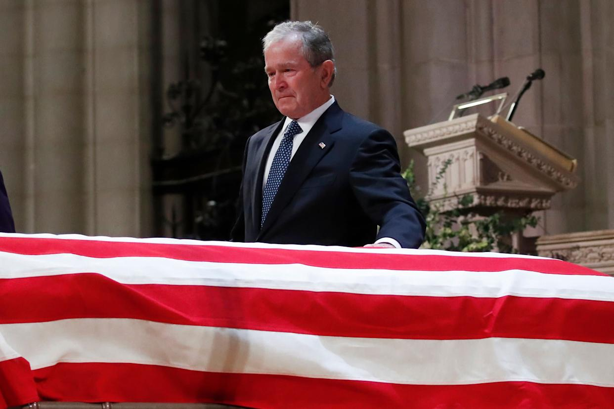 Former President George W. Bush touches the casket of his father, former President George H.W. Bush, at the State Funeral at the Washington National Cathedral.