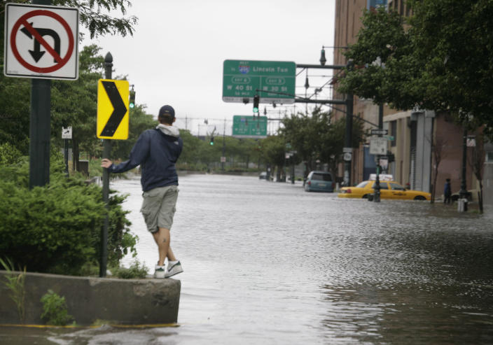 FILE - In this file photo of Aug. 28, 2011, a man surveys the floodwaters on Manhattan's West Side after Hurricane Irene, downgraded to a tropical storm, hit New York. Two years before Irene created the prospect of a flooding nightmare in New York City, 100 scientists and engineers met to sketch out a bold defense: Massive, moveable barriers to shield the city from a storm-stirred sea.(AP Photo/Peter Morgan, File)