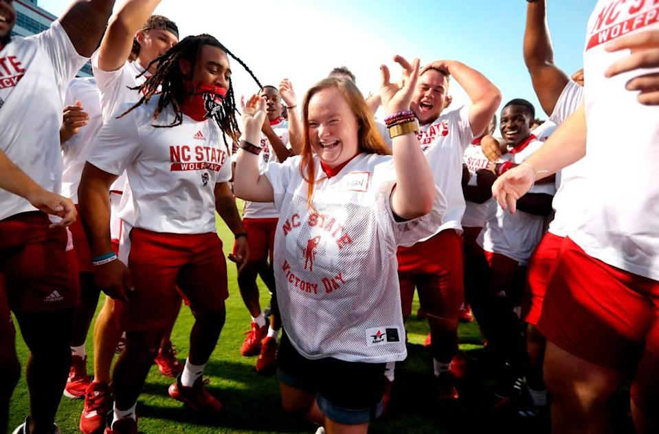 """Megan Czejkowski of Raleigh celebrates scoring a touchdown with N.C. State football players during """"Victory Day"""" with the Wolfpack at Carter-Finley Stadium in Raleigh, N.C., Saturday, August 7, 2021. The Wolfpack partnered with GiGi's Playhouse Raleigh, a Down's syndrome achievement center, to let participants enjoy a game day experience with players."""