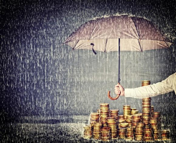 An umbrella protects a pile of gold coins from the rain.