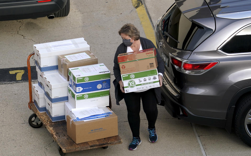 Election officials from around Dane County bring ballots in, Thursday, Nov., 19, 2020 to the Monona Terrace in Madison, Wis. for the recount that begins Friday. (Steve Apps/Wisconsin State Journal via AP)