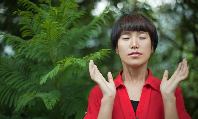 Woman doing deep breathing exercise in nature (posed by model)