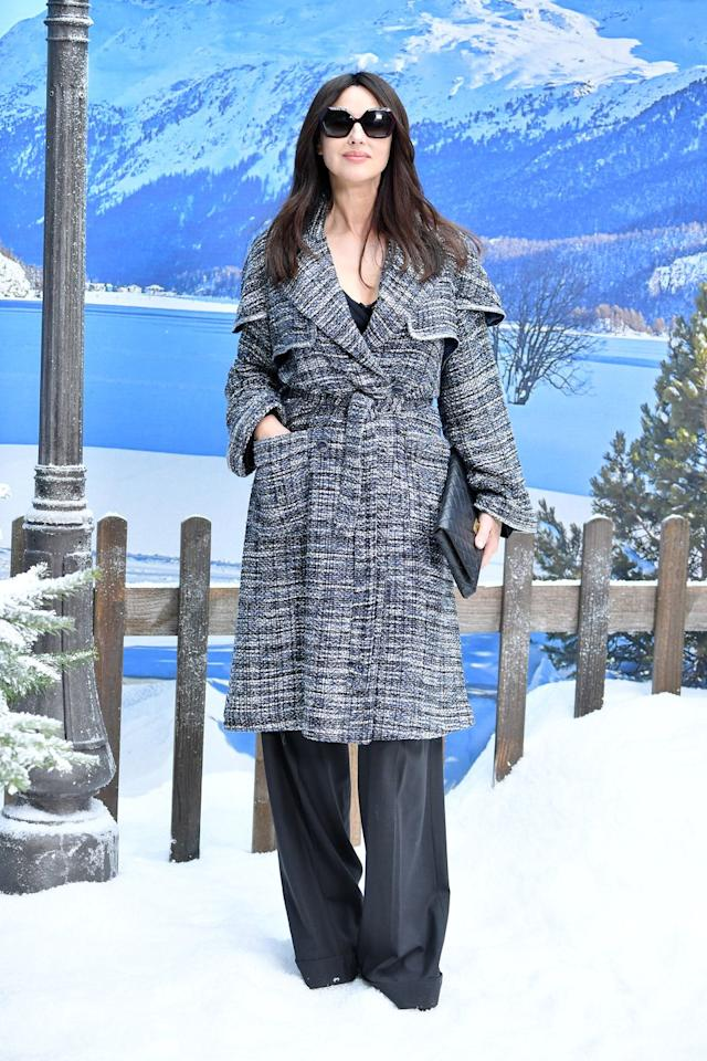 <p>Monica Bellucci wrapped up in a tweed belted coat and wide-leg trousers. </p>