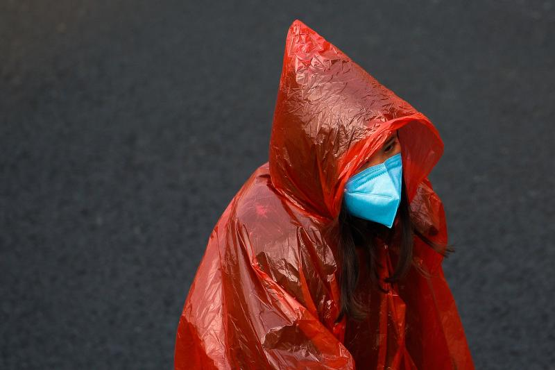 <strong>A masked woman in a plastic rain coat walks on a street in Beijing, Tuesday, Feb. 11.</strong> (Photo: ASSOCIATED PRESS)