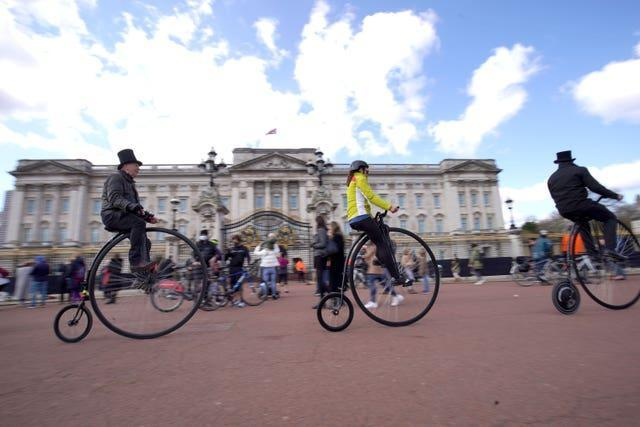 People ride penny farthings past Buckingham Palace