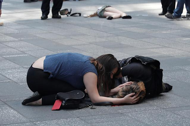 <p>A woman attends to an injured man on the sidewalk in Times Square after a speeding vehicle struck pedestrians on the sidewalk in New York City on May 18, 2017. (Mike Segar/Reuters) </p>