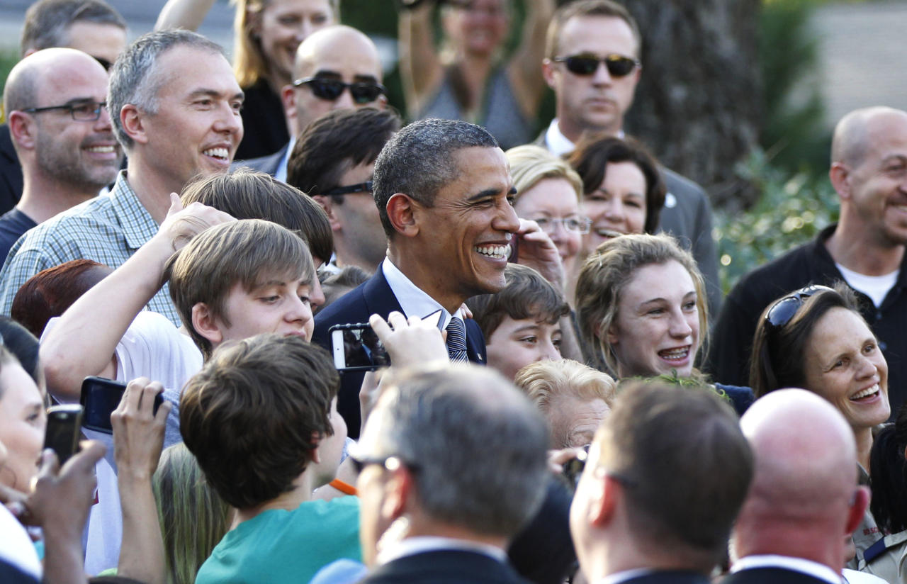 President Barack Obama, center, stops to take a group picture with neighborhood residents in Atlanta, Friday, March, 16, 2012. Obama is attending a private fundraiser across the street when he made this unannounced stop to get out and greet people. (AP Photo/Pablo Martinez Monsivais)