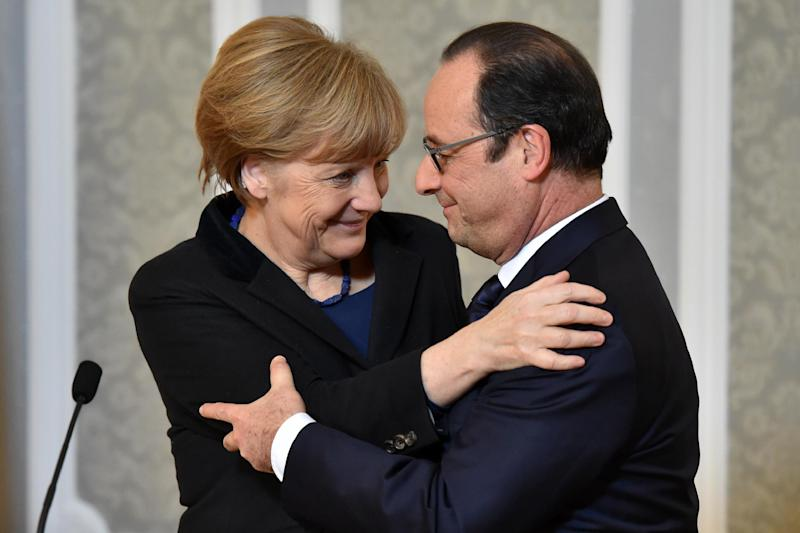 France's President Francois Hollande (R) and German Chancellor Angela Merkel hug each other during a press conference after a summit on Ukraine, in Minsk on February 12, 2015 (AFP Photo/Kirill Kudryavtsev)