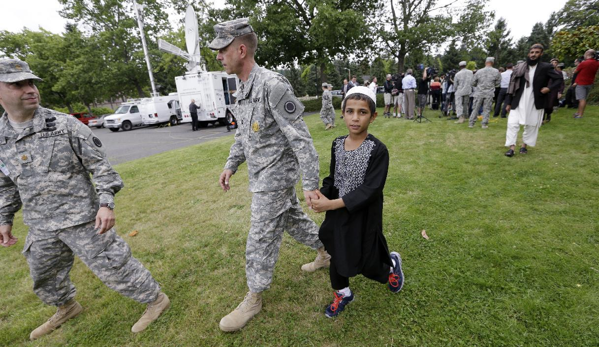A young Afghan villager boy named Khan holds the hand of U.S. Army Master Sgt. Timothy Gunther following a news conference with other villagers after a sentencing hearing for Staff Sgt. Robert Bales at Joint Base Lewis-McChord, Wash., on Friday, Aug. 23, 2013. Bales, who massacred 16 Afghan civilians in 2012 in one of the worst atrocities of the Iraq and Afghanistan wars, was sentenced Friday to life in prison with no chance of parole. (AP Photo/Elaine Thompson)
