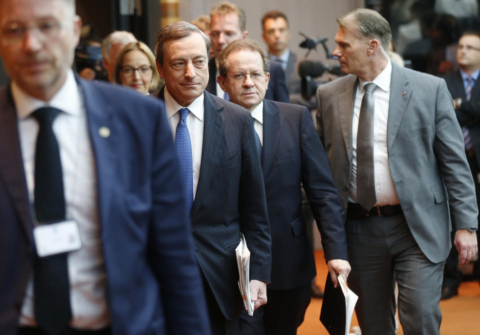 President of European Central Bank, Mario Draghi ,  second left,  is on the way to a news conference in Frankfurt, Germany, Thursday, June 5, 2014,.  The European Central Bank has cut two key interest rates, one of them into negative territory — a highly unusual step that underlines the urgency of its efforts to keep the eurozone economy from sliding into crippling deflation. It reduced its main interest rate, the refinancing rate, from a record low of 0.25 percent to 0.15 percent. More drastically, it also cut the rate it pays on money deposited by banks from zero to minus 0.1 percent, an unprecedented step for the ECB that aims to push banks to lend money rather than hoard it.   (AP Photo/Michael Probst)