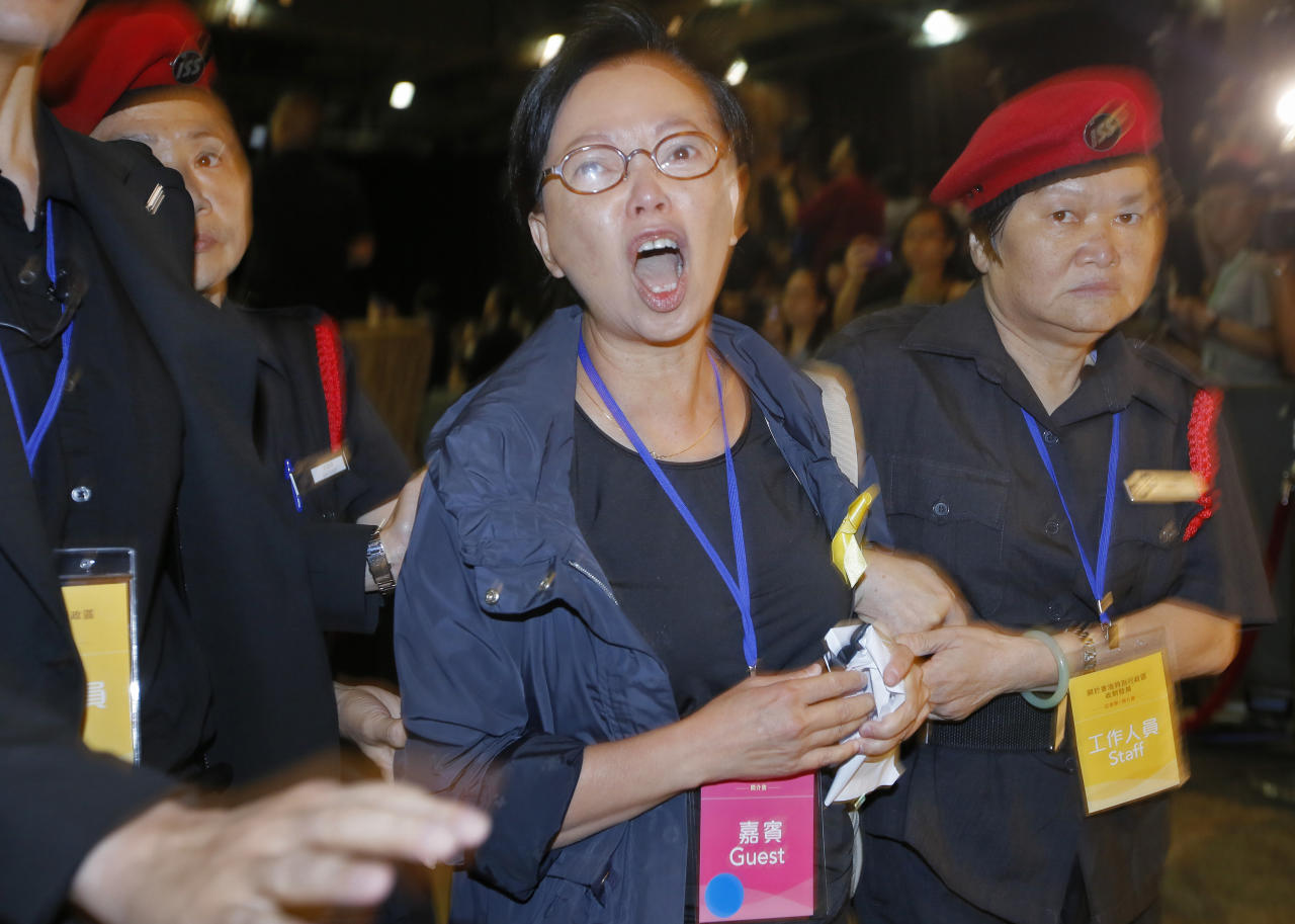 "Pro-democracy lawmaker Cyd Ho, center, is taken away by security guards after a protest against Li Fei, deputy secretary general of the National People's Congress Standing Committee, in Hong Kong Monday, Sept. 1, 2014. China's legislature on Sunday ruled out allowing open nominations in the inaugural election for Hong Kong's leader, saying they would create a ""chaotic society."" Democracy activists in the Asian financial hub responded by saying that a long-threatened mass occupation of the heart of the city ""will definitely happen."" (AP Photo/Vincent Yu)"