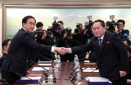 Head of the North Korean delegation, Ri Son Gwon shakes hands with South Korean counterpart Cho Myoung-gyon as they exchange documents after their meeting at the truce village of Panmunjom in the demilitarised zone separating the two Koreas.    Yonhap via REUTERS