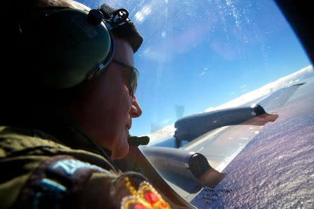 Wyatt looks out an observation window aboard a RNZAF P3 Orion maritime search aircraft as it flies over the southern Indian Ocean looking for debris from missing Malaysian Airlines flight MH370