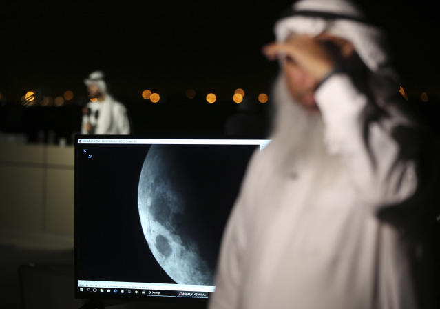 <p>The lunar eclipse is shown on a screen at the Al Thuraya Astronomy Center in Dubai, United Arab Emirates, Friday, July 27, 2018. (Photo: Kamran Jebreili/AP) </p>
