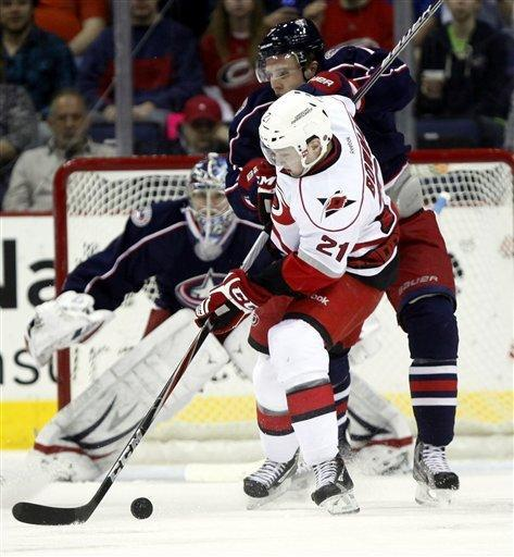 Carolina Hurricanes' Drayson Bowman (21) is checked by Columbus Blue Jackets' Jack Johnson, right rear, as Jackets goalie Steve Mason look on, during the second period of an NHL hockey game on Friday, March 23, 2012, in Columbus, Ohio. The Blue Jackets won 5-1. (AP Photo/Terry Gilliam)