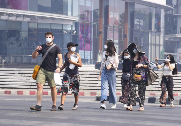 Tourists wear masks in Chiang Mai province, Thailand, Tuesday, April 2, 2019. The air hanging over Thailand's far north has become so polluted, the prime minister went Tuesday to see in person what's been called a severe health crisis. (AP Photo/Maytanan Merchant)