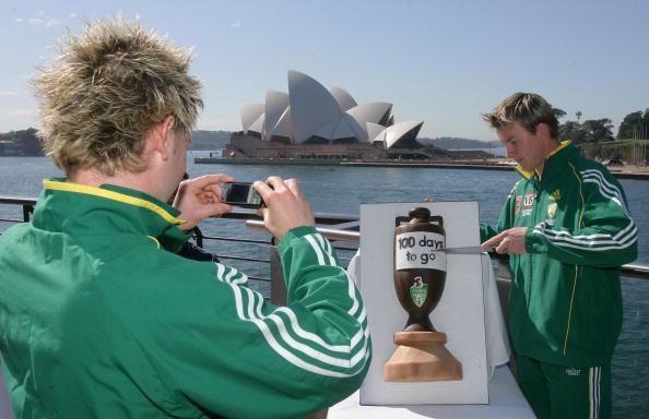 SYDNEY, AUSTRALIA - AUGUST 15: Australian cricketer Michael Clarke (L) takes a photograph of team mate Brett Lee as he cuts into a cake baked in the shape of the ashes urn at the 100 day countdown launch for the up coming Ashes series held at Circular Quay August 15, 2006 in Sydney, Australia. (Photo by Chris McGrath/Getty Images)