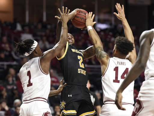 Wichita State's Jamarius Burton (2) shoots as Temple Quinton Rose (1) and Arashma Parks (14) defend during the first half of an NCAA college basketball game Wednesday, Jan. 15, 2020, in Philadelphia. (AP Photo/Michael Perez)