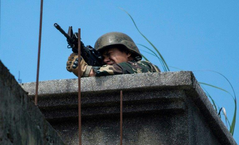 A Philippine soldier takes aim at militant positions from a rooftop in Marawi on June 13, 2017
