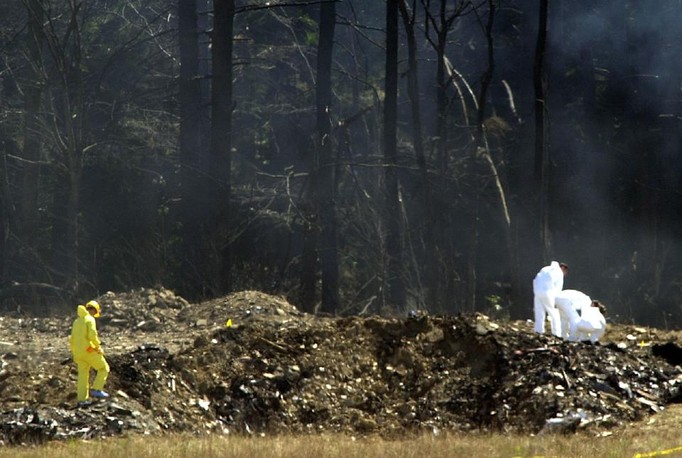 Smoke rises behind investigators as they comb the crater left by the crash of United Airlines flight 93 near Shanksville, Pennsylvania September 12, 2001. Flight 93 is one of four planes that were hijacked as part of a deadly and destructive terrorist plot against the U.S. September 11. REUTERS/Tim Shaffer  TMS