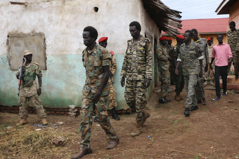 "FILE - In this Tuesday, May 30, 2017 file photo, South Sudanese soldiers accused of gang-raping five foreigners, murdering a local journalist and looting a hotel, are led to their prison van after attending a hearing of their trial in the capital Juba, South Sudan. The latest report on human rights abuses in South Sudan's five-year civil war, released by a United Nations commission Friday, Feb. 23, 2018 says it has identified more than 40 senior military officials ""who may bear individual responsibility for war crimes."" (AP Photo/Bullen Chol, File)"
