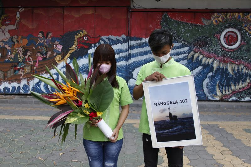 People holding a placard and flowers bow as they pray for the crew of submarine KRI Nanggala-402 which has sunk at the north of Bali sea, during a vigil in Solo