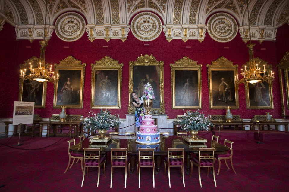 LONDON, ENGLAND - JULY 24:   Anna Reynolds, curator of Royal Collection Trust, puts the finishing touches to a display of the 1853 christening cake of Prince Leopold in the State Dining Room of Buckingham Palace, which features in a new exhibition exploring 250 years of royal childhood on July 24, 2014 in London, England. The exhibition, which opens to the public on July 26 and runs until September 28 features childhood toys, family gifts and outfits belonging to the Royal family dating back 250 years.  (Photo by Oli Scarff/Getty Images)
