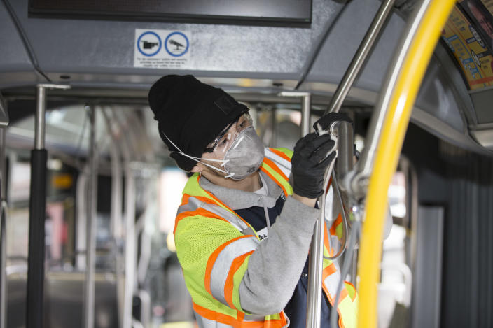 A utility service worker deep cleans a bus in Seattle, Wash., in early March. Here's how to know what precautions your state may be taking to keep you safe. (Photo: Karen Ducey/Getty Images)