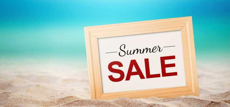 """A sign saying """"Summer Sale"""" resting on a beach"""