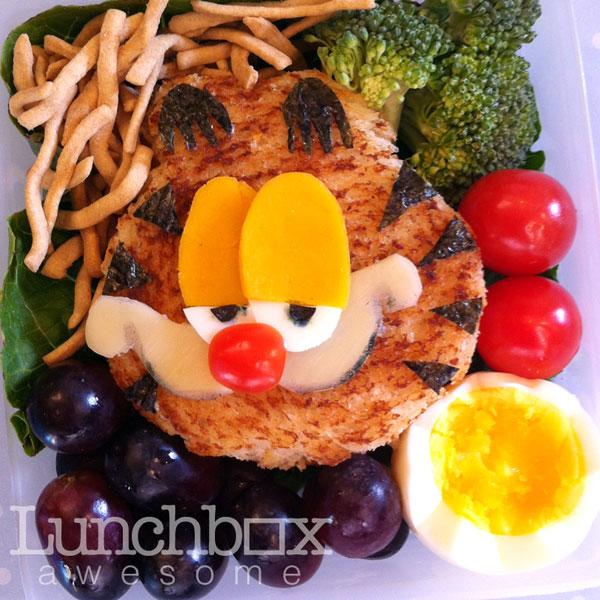 """After finding some ideas for recipes on how to manipulate food into shapes and patterns online Heather began to create the bento-style lunches for her son for fun. She then posted them Facebook for friends and family to see and since then all of her creations have been documented on her blog <a target=""""_blank"""" href=""""http://lunchboxawesome.tumblr.com/"""">Lunchbox Awesome</a>.<br><br>Heather is a huge fan of children's cartoons. Here she has crafted Garfield's sleepy expression using some egg yolk and whites and a piece of whole grain toast with seaweed for the cat's stripes.<br><br>Photo: Heather Sitarzewski"""