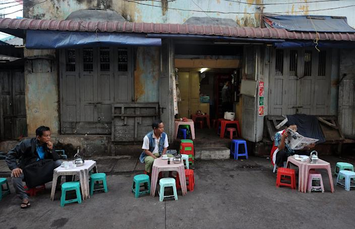 Customers sit with drinks at a traditional roadside coffee shop in downtown Yangon, January 28, 2015 (AFP Photo/Soe Than Win)