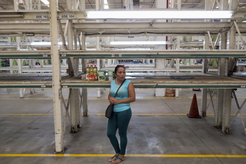 A woman stands with oil and detergent next to empty shelves inside a Makro supermarket in Caracas January 9, 2015. Lines are swelling at Venezuelan supermarkets, with some shoppers showing up before dawn in search of products ranging from chicken to laundry detergent, as a holiday slowdown in deliveries sharpened the nation's nagging product shortages. Queues snaked around the block at grocery stores and pharmacies around the country on Friday, with consumers in some cases gathering before dawn under the gaze of National Guard troops posted to maintain order. REUTERS/Jorge Silva (VENEZUELA - Tags: BUSINESS POLITICS FOOD SOCIETY TPX IMAGES OF THE DAY)