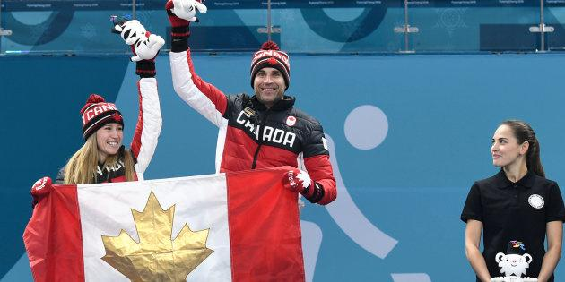 Canada's Kaitlyn Lawes and John Morris celebrate on the podium during the curling mixed doubles venue ceremony.