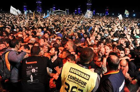 People are pressed against the security barricade in the mosh pit area during a show of Argentine singer Indio Solari in Olavarria