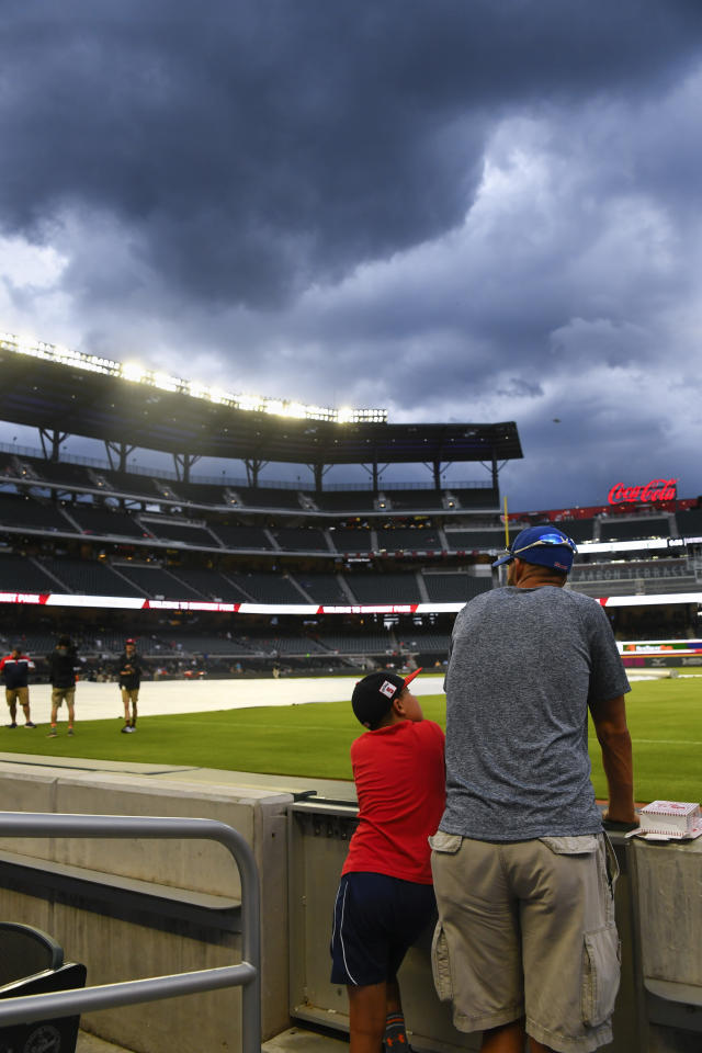 Fans look over the field as clouds linger over SunTrust Park before the start of a baseball game between the Atlanta Braves and New York Mets, Wednesday, Aug. 14, 2019, in Atlanta. The start of the game is delayed due to the weather. (AP Photo/John Amis)