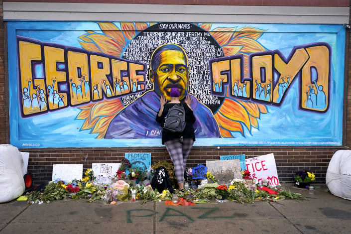 """FILE - In this Friday, April 23, 2021 file photo, Damarra Atkins pays respect to George Floyd at a mural at George Floyd Square in Minneapolis. Newly released video that shows Minneapolis police officers talking about """"hunting people"""" during unrest following the death of George Floyd is now becoming an issue in the upcoming citywide election as Mayor Jacob Frey seeks a second term and residents will vote on whether they want to replace the police department with a new agency. (AP Photo/Julio Cortez, File)"""
