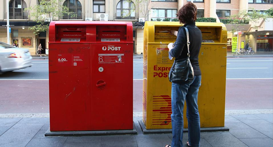 A woman mailing post into an Express Post Letter box