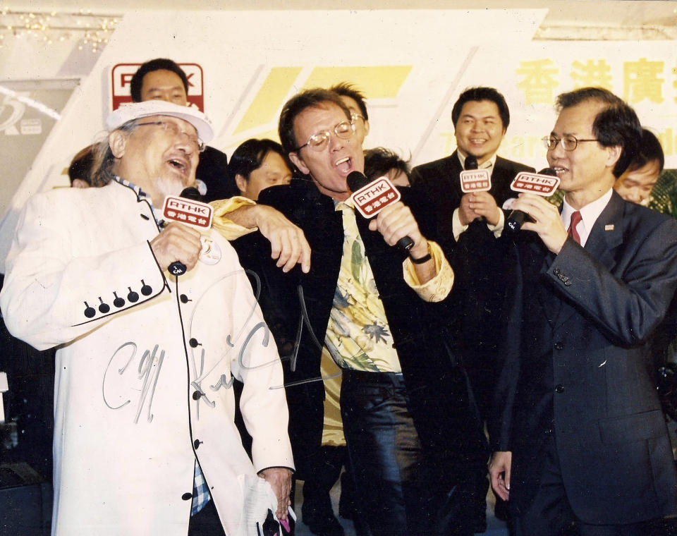 """In this undated photo released by Radio Television Hong Kong (RTHK), Hong Kong DJ, Ray Cordeiro, also known as Uncle Ray, left, performs with Cliff Richard, center, at an event to celebrate the 75th Anniversary of Broadcasting in Hong Kong. After more than seven decades in radio, the 96-year-old Hong Kong DJ bid farewell to his listeners Saturday, May 15, 2021 with """"Time to Say Goodbye,"""" sung by Sarah Brightman and Andrea Bocelli. (Radio Television Hong Kong via AP)"""