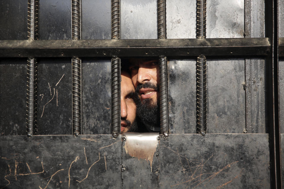 Taliban prisoners watch through the door inside the prison after an attack in the city of Jalalabad, east of Kabul, Afghanistan, Monday, Aug. 3, 2020. An Islamic State group attack on the prison in eastern Afghanistan holding hundreds of its members raged on Monday after killing people in fighting overnight, a local official said. (AP Photo/Rahmat Gul)
