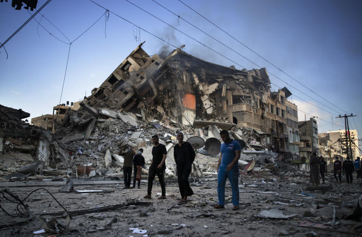 Palestinians walk next to the remains of a destroyed 15 story building after being hit by Israeli airstrikes on Gaza City, Thursday, May 13, 2021. (AP Photo/Khalil Hamra)