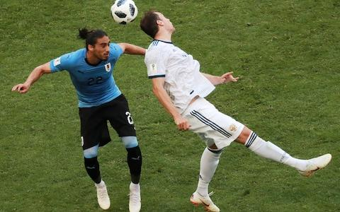 Uruguay's Martin Caceres (L) and Russia's Artyom Dzyuba in action in their 2018 FIFA World Cup Group A football match at Samara Arena Stadium - Credit: Getty Images