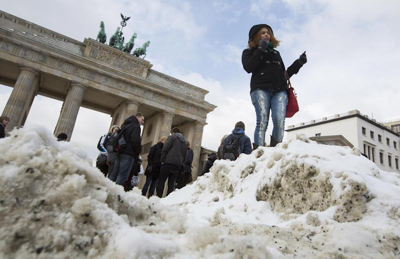 A tourist stands  in front of Brandenburg Gate to pose for a souvenir photo as the sun shines through the  clouds in Berlin, Germany, Tuesday, March 12, 2013. As fresh snow fell in wide parts of western Germany the airport in Frankfurt was closed after about 12 centimeters (5 inches) of snow and the airport had already canceled more than 100 flights and reported many delays. (AP Photo/Gero Breloer)