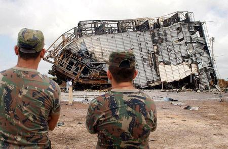 FILE PHOTO: Brazilian soldiers look on as technicians inspect the damage of what's left of the Alcantara launch pad, on Brazil's Amazon jungle coast, August 25, 2003. REUTERS/Agencia Brasil/File photo