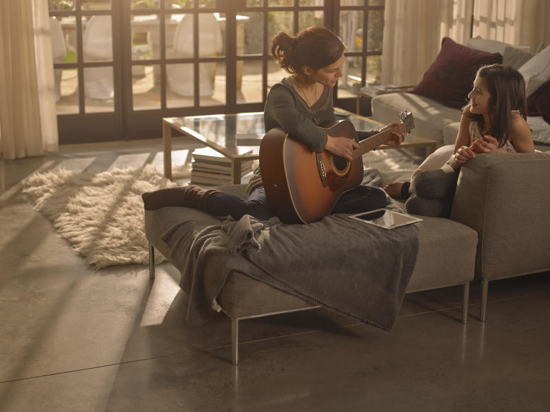 Woman on a sofa practising the guitar with her daughter.