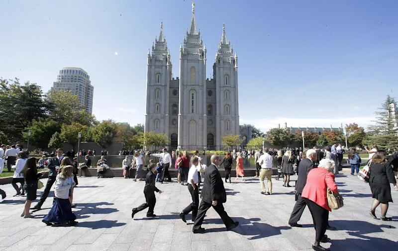 FILE - In this Oct. 5, 2013, file photo, shows people walking pass the Salt Lake Temple on the way to the Conference Center during opening session of the two-day Mormon church conference, in Salt Lake City. More than 100,000 Latter-day Saints are expected in Salt Lake City this weekend for the church's biannual general conference. Leaders of The Church of Jesus Christ of Latter-day Saints give carefully crafted speeches aimed at providing members with guidance and inspiration in five sessions that span Saturday and Sunday. They also make announcements about church statistics, new temples or initiatives. In addition to those filling up the 21,000-seat conference center during the sessions, thousands more listen or watch around the world in 95 languages on television, radio, satellite and Internet broadcasts. A Mormon's women group pushing the church to allow women in the priesthood plans to demonstrate outside an all-male meeting Saturday. The church has asked them to reconsider, and barred media from going on church property during the demonstration. (AP Photo/Rick Bowmer, File)